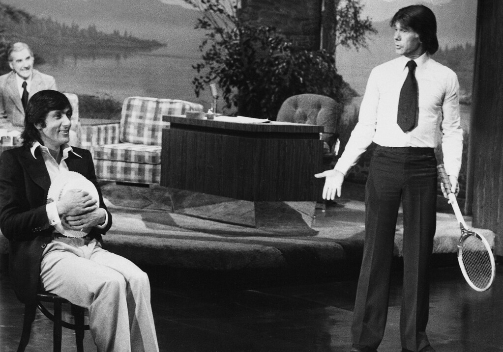 """. Ilie Nastase, left, professional tennis champion, plays the part of a tennis lineman as talk show host Johnny Carson, right, portrays the sometimes tempermental Nastase in a skit during taping of the \""""Tonight Show\"""" in Los Angeles, Calif., Friday night, Sept. 25, 1976.  Program announcer Ed McMahon is in background, left.  (AP Photo)"""