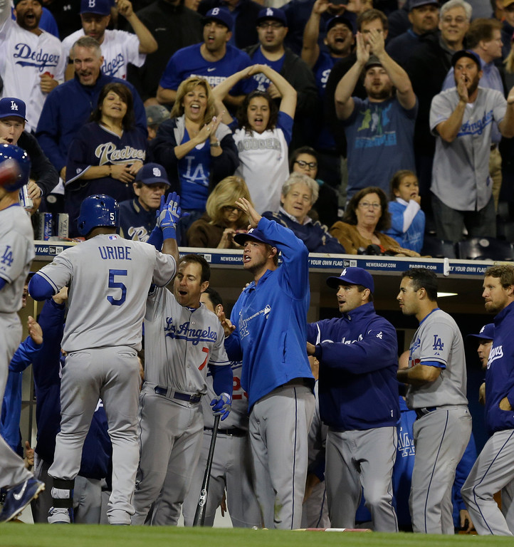 . Los Angeles Dodgers\' Juan Uribe is greeted by team,mates and cheering fans after his solo home run gave the Dodgers a one run lead over the San Diego Padres during the eighth inning of baseball game marred by a braw between the teams in San Diego, Thursday, April 11, 2013. (AP Photo/Lenny Ignelzi)
