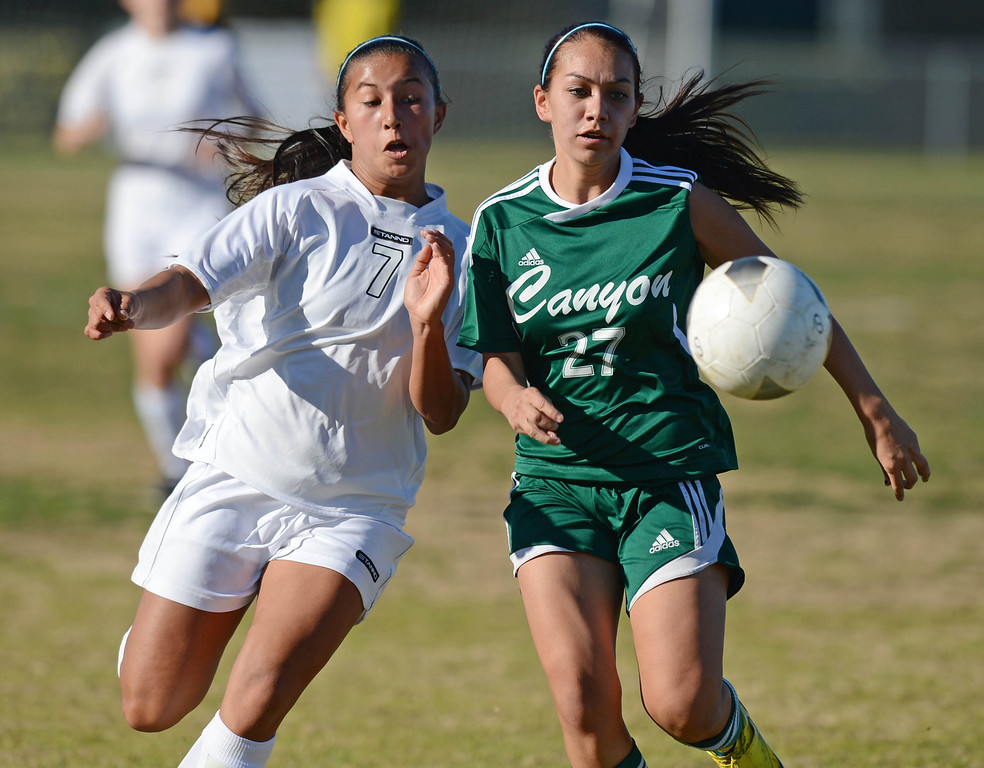 . Peninsula\'s Katie Bumatay (7) and Canyon\'s Alissa Munguia (27) race for the ball in a CIF SS Division II first round soccer game Thursday in Rolling Hills Estates. After Peninsula seemingly dominated most of the game, Canyon scored a goal in the final two minutes to win 1-0. 20130214 Photo by Steve McCrank / Staff Photographer