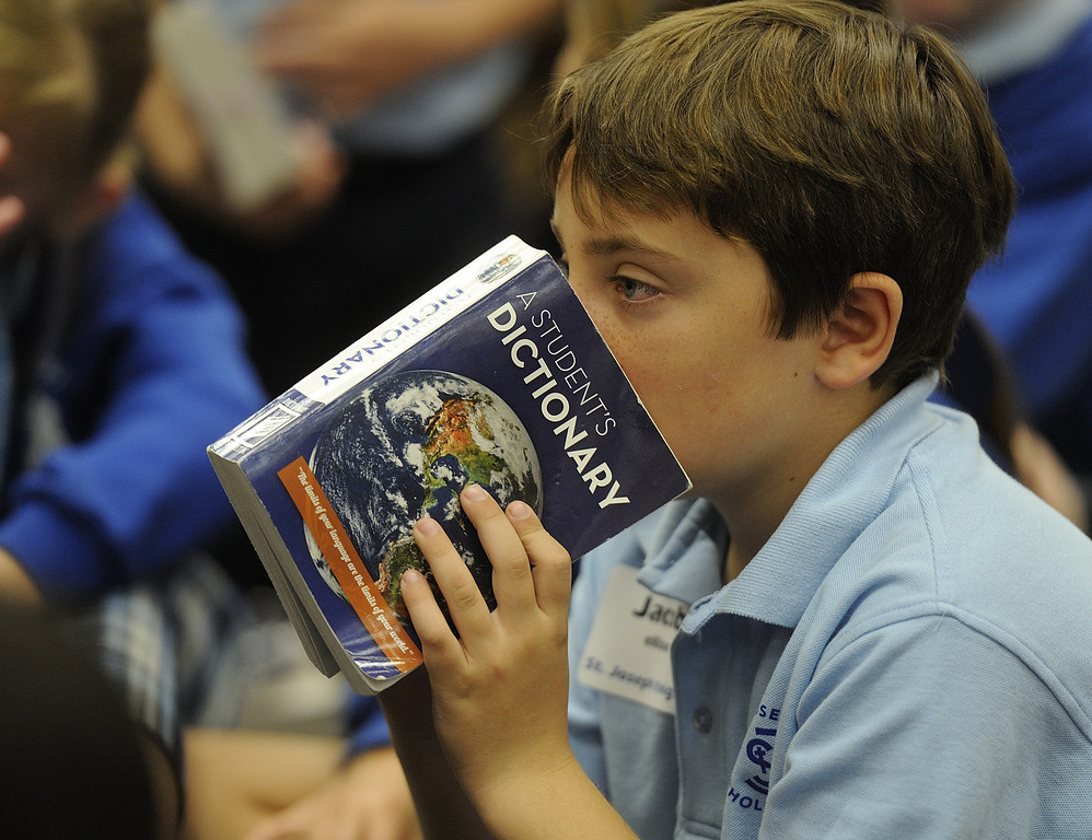 """. LONG BEACH, CALIF. USA -- St. Joseph third grader Jacob Ellison buries his nose in his dictionary during a game at the El Dorado Beach Library in Long Beach, Calif., on February 28, 2013. This is the 10th. year that dictionaries have been purchased and distributed to third-grade students in the Long Beach Unified School District, charter, local parochial and private schools. The Long Beach Dictionary Project promotes literacy and the goal that all students will leave third-grade at the end of the year as \""""good writers, active readers, and creative thinkers\"""". The Miller Foundation, which has been providing dictionaries to third-graders since 2003, is celebrating giving away its 100,000 lexicon literary. Photo by Jeff Gritchen / Los Angeles Newspaper Group"""