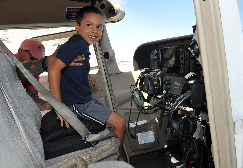 ". 8/21/13 - Vicente Valenzuela, 7, hops into the driver seat of a Cesna on Wednesday afternoo . Pediatric rehabilitation patients from Miller Children�s Hospital Long Beach got experience their first �Discovery Flight� at the California Flight Center. After some training from the pilots the kids got to actually pilot the plane on their own. The program which uses volunteer pilots has taken 125 kids in the air. Valenzuela  who suffers from autism liked ""pulling back on the steering wheel,\"" best of all. Photo by Brittany Murray, Press Telegram"