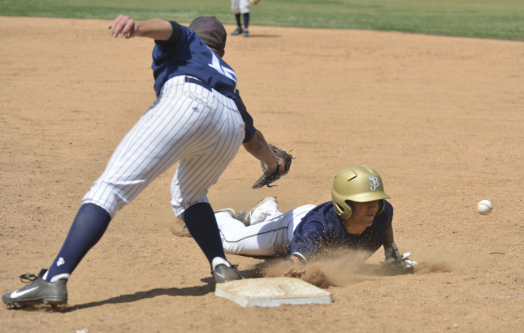 . SANTA FE SPRINGS, CALIF. USA -- St. John Bosco\'s Michael Thomas (9) dives back in to first base as St. Paul\'s Kevin Lugo (10) misses the ball allowing Thomas to take second base. He later scored the first run of the game during their game at the St. Paul Tournament in Santa Fe Spring, Calif., on March 2, 2013. St. John Bosco defeated St. Paul, 4 to 2. Photo by Jeff Gritchen / Los Angeles Newspaper Group