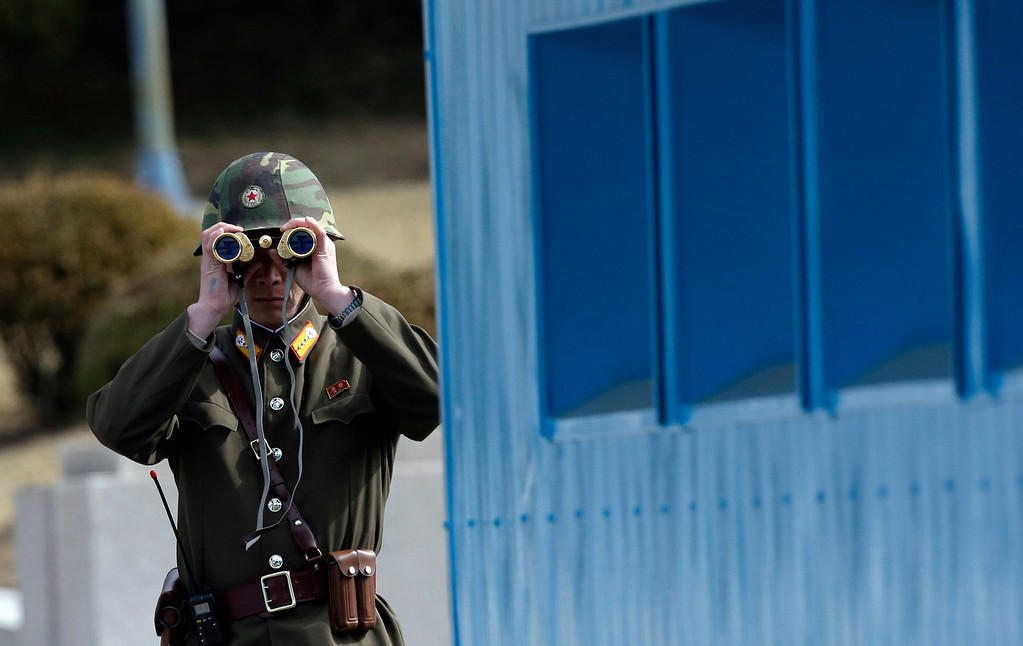 . A North Korean soldier looks at the southern side through a pair of binoculars at the border village of the Panmunjom (DMZ) that separates the two Koreas since the Korean War, in Paju, north of Seoul, South Korea, Tuesday, March 19, 2013. The United States is flying nuclear-capable B-52 bombers on training missions over South Korea to highlight Washington\'s commitment to defend an ally amid rising tensions with North Korea, Pentagon officials said Monday.(AP Photo/Lee Jin-man)