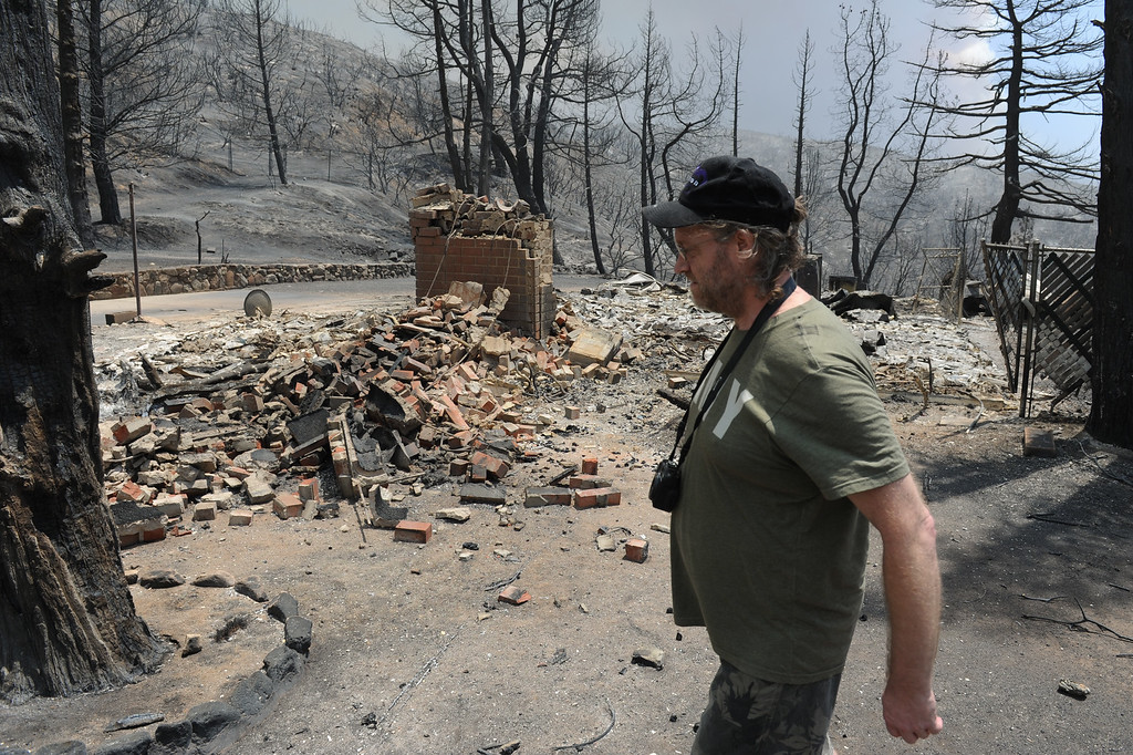 . Lake Hughes resident Jonathan Pehrson walks by a burnt house on Newview Drive in Lake Hughes from the Powerhouse Fire, Sunday, June 2, 2013. Pehrson\'s home survived the fire. (Michael Owen Baker/Staff Photographer)