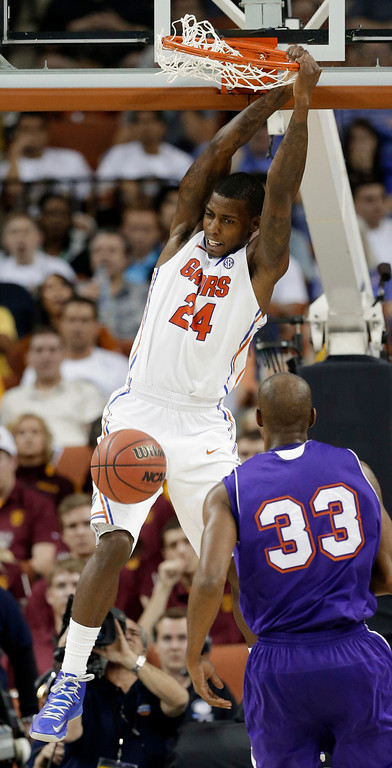 . Florida\'s Casey Prather (24) hangs on the rim after dunkingas Northwestern State\'s James Hulbin (33) watches during the second half of a second-round game of the NCAA men\'s college basketball tournament Friday, March 22, 2013, in Austin, Texas. Florida won 79-47. (AP Photo/David J. Phillip)