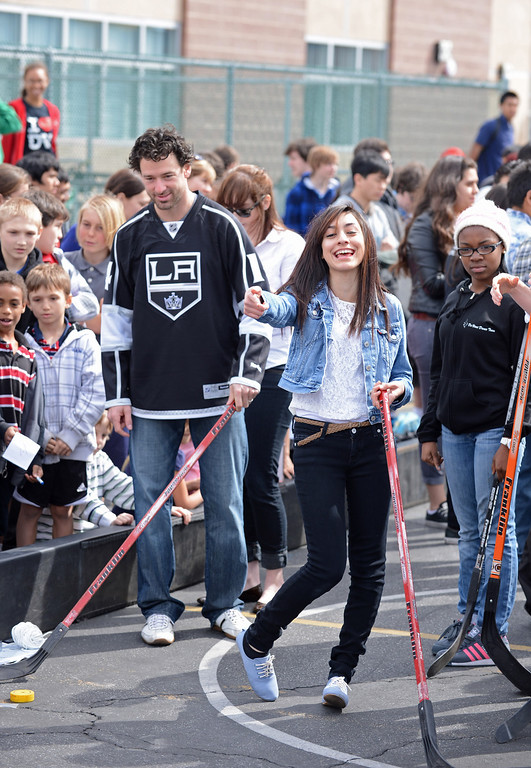 . LA Kings players Justin Williams, #14, watches Daisy Chavez, 11th grade, shoot to the goal at DaVinci High School in Hawthorne .   Photo by Brad Graverson 3-8-13
