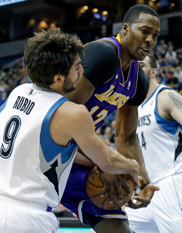 . Los Angeles Lakers\' Dwight Howard, right, and Minnesota Timberwolves\' Ricky Rubio of Spain battle for possession of the ball in the first quarter of an NBA basketball game Wednesday, March 27, 2013 in Minneapolis. (AP Photo/Jim Mone)