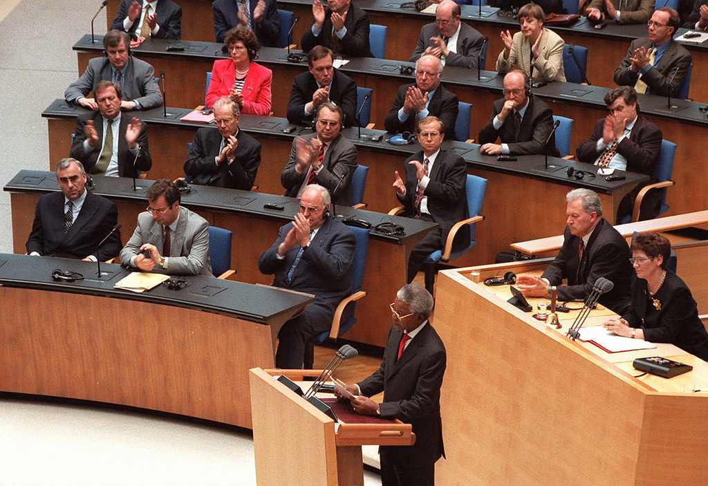 . South African President Nelson Mandela addresses the German parliament while Chancellor Kohl and his ministers applaude in Bonn Wednesday, May 22, 1996. At right is the President of the Parliament Rita Suessmuth. In the first row, from right, Chancellor Helmut Kohl, Foreign Minister Klaus Kinkel and Finance Minister Theo Waigel. (AP PHOTO/Hermann Knippertz)