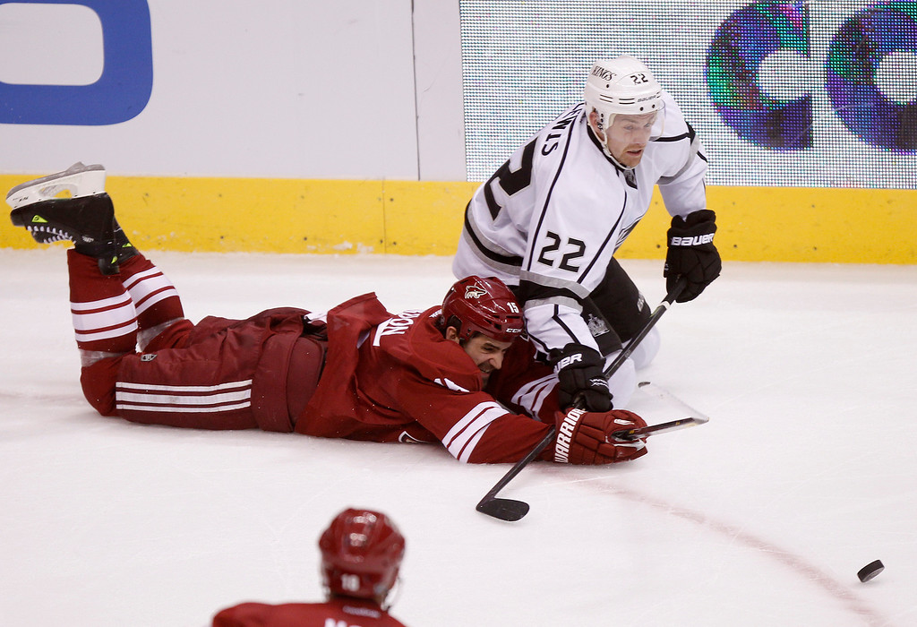 . Phoenix Coyotes center Boyd Gordon, bottom, dives to poke the puck away from Los Angeles Kings center Trevor Lewis, top, in the third period of an NHL hockey game Tuesday, April 2, 2013, in Glendale, Ariz. The Coyotes won 3-1. (AP Photo/Paul Connors)