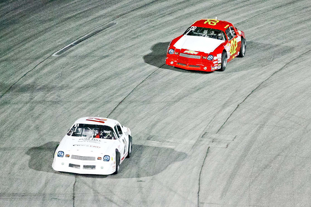 . Zack Green (21) leads Gary Read (02) out of turn 4 in opening night of racing at Irwindale Speedway Saturday April 6, 2013. (Correspondent photo by Chris Burt)