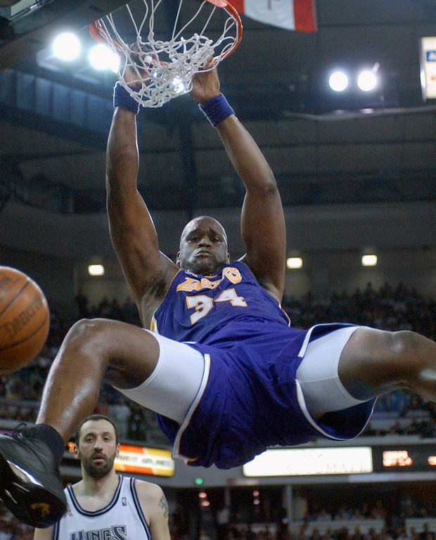 . Los Angeles Lakers\' Shaquille O\'Neal hangs from the rim after dunking as Sacramento Kings\' Vlade Divac, left, looks on during the first half of Game 2 of the Western Conference finals Monday, May 20, 2002, in Sacramento, Calif.  (AP Photo/Kevork Djansezian)