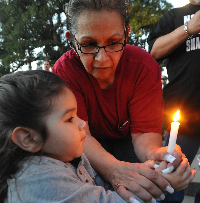 . Susan Dominguez helps Joshua Dominguez, 2-1/2, hold a candle during a community-wide prayer vigil at Central Park in Whittier in response to recent attempted child abductions on Friday March 15, 2013. About 150 people attended the candlelight vigil led by Pastor Sam Gamboa of the Good Shepherd Family Bible Church and organized by the Whittier Area Evangelical Ministerial Alliance. City and police officials joined citizens and area church members as they prayed for protection of the children and the arrest of the suspects. (SGVN/Staff Photo by Keith Durflinger)
