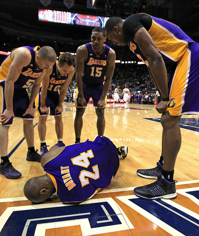 . Los Angeles Lakers\' Steve Blake, from left, Steve Nash, Metta World Peace and Dwight Howard gather around Kobe Bryant as he lays on the floor after being injured in the final seconds of an NBA basketball game against the Atlanta Hawks on Wednesday, March 13, 2013, in Atlanta. The Hawks defeated the Lakers 96-92.  (AP Photo/Atlanta Journal-Constitution, Curtis Compton)