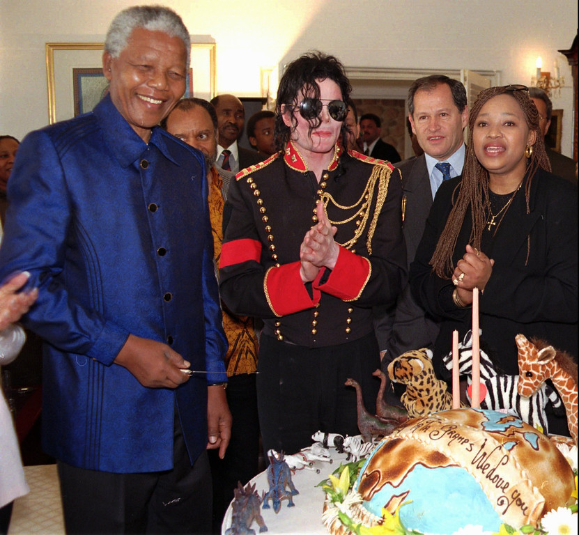 ". American pop star Michael Jackson, center, applauds South African President Nelson Mandela, after singing ""Happy Birthday\"" to him at a private birthday function for the president at his Johannesburg home Thursday, July 18, 1996. Mandela\'s daughter Zinzi is seen at right. Jackson is on a four day trip to South Africa. (AP Photo/Sipiwe Mhlambi)"