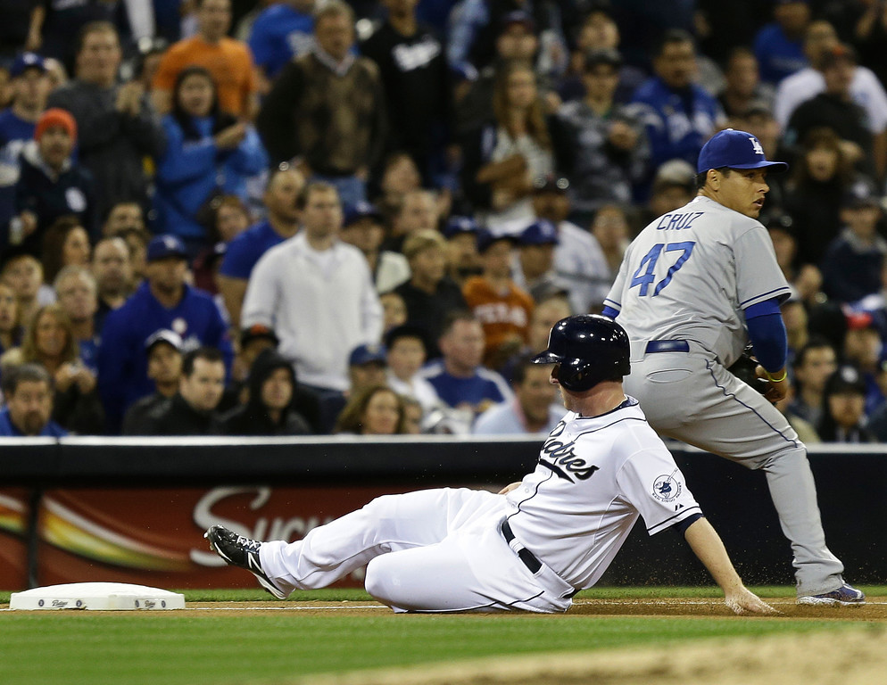 . San Diego Padres\' Jedd Gyorko slides safely into third as Los Angeles Dodgers third baseman Luis Cruz takes in a late throw during the fourth inning  of a baseball game in San Diego, Thursday, April 11, 2013. Gyorko was advancing from first on a based hit by Nick Hundley and would score moments later on a wild pitch. (AP Photo/Lenny Ignelzi)