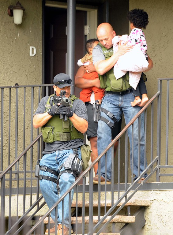 Description of . Deputies evacuate residents from their apartment homes while searching looking for a suspected gunman. (LaFonzo Carter/ Staff Photographer