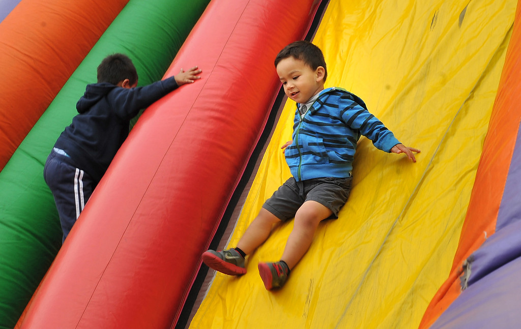 . 5/25/13 - Diego Mendoza, 2 1/2 enjoys the bouncy slide while his older brother prepares for the 1-mile fun run at the Children Today\'s 5th Annual run/walk at Marina Green Park. The local non-profit, Children Today, is an organization that provides for families and children experiencing homelessness in Long Beach. They\'ve raised $33,184 and their final goal is $50,000. Photo by Brittany Murray / Staff Photographer