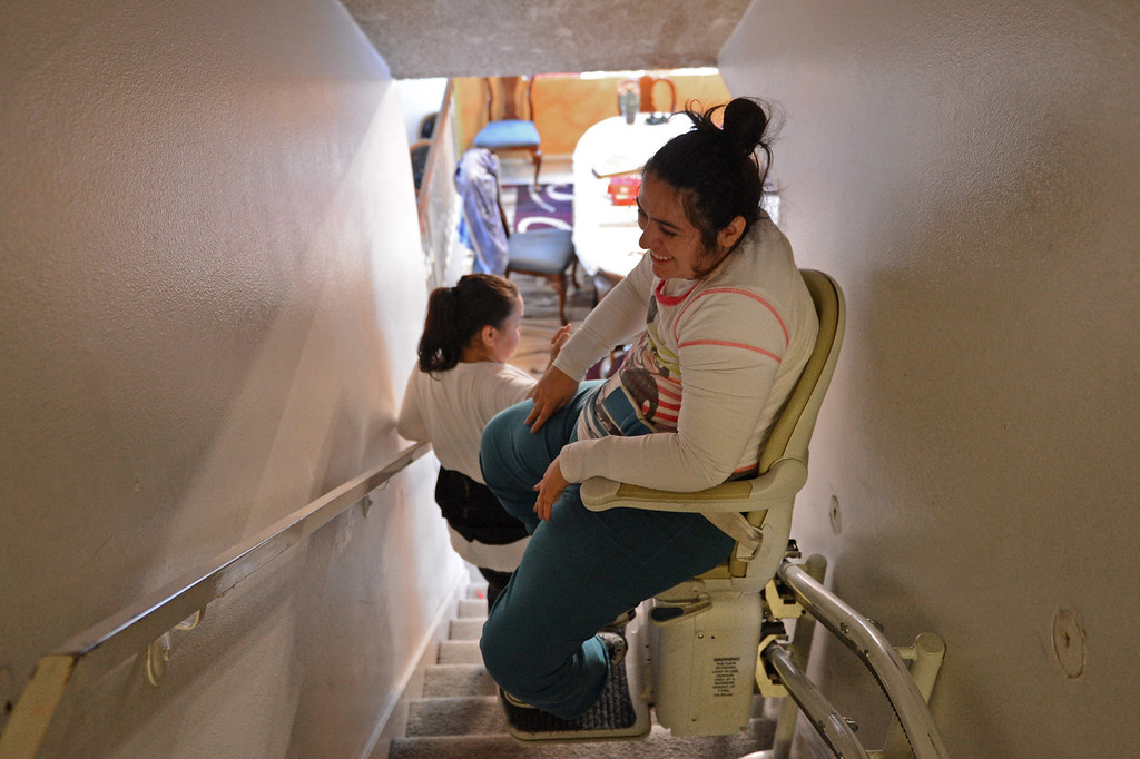 . A motorized chair moves Olivia down the stairs of her Torrance home. Photo by Brad Graverson/LANG 1-29-13