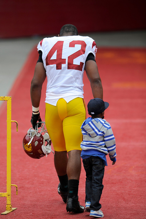 . DE Devon Kennard walks off the field with his nephew Derek Kennard at USC\'s Spring Football Game. (Michael Owen Baker/Staff Photographer)