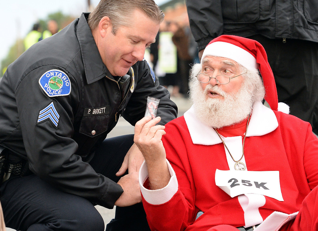 . Walmart protester Karl Hilgert hands Ontario police department Sgt Pat Birkett a candy cane as Hilgert is read his rights before being arrested for failure to disperse after sitting down with 9 other protesters in the middle of the intersection at 5th and Mountain Avenues in Ontario Friday morning November 29, 2013. Over 100 protesters came to the Walmart on Mountain Avenue to protest against Walmart\'s wages and benefits.   (Will Lester/Inland Valley Daily Bulletin)
