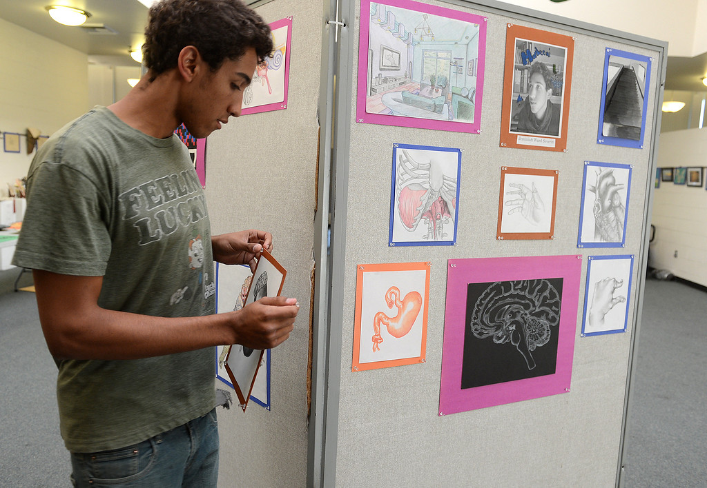 . Jeremiah Ward Severin pins up his art work as the Upland High School\'s visual and performing arts students showcase their work during their annual show in Upland April 26, 2013. (Thomas R. Cordova/Staff Photographer)