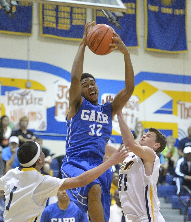 . LONG BEACH, CALIF. USA -- Gahr\'s David Murrell (32) comes down with a rebound against Millikan\'s Thomas Pua (1) and Jacob Lundi-Mallett (21) during their CIF-SS Divison 1-A playoff game in Long Beach on February 15, 2013. Millikan defeated Gahr, 74 to 64. Photo by Jeff Gritchen / Los Angeles Newspaper Group