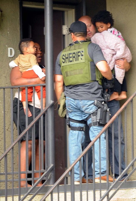 Description of . Deputies evacuate residents from their apartment homes while searching looking for a suspected gunman. (LaFonzo Carter/ Staff Photographe