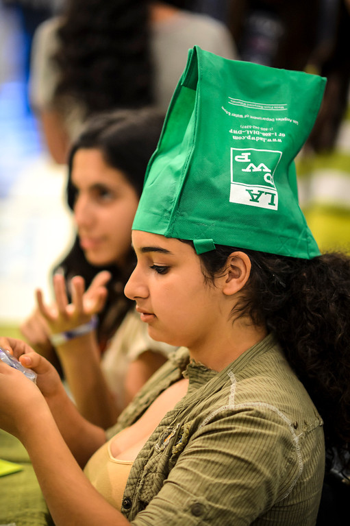 . Portola Middle school student Meray Beddian, 13, recycles a DWP shopping bag as a hat while passing out literature for Earth Day at the Tarzana school.    Photo by David Crane/Staff Photographer