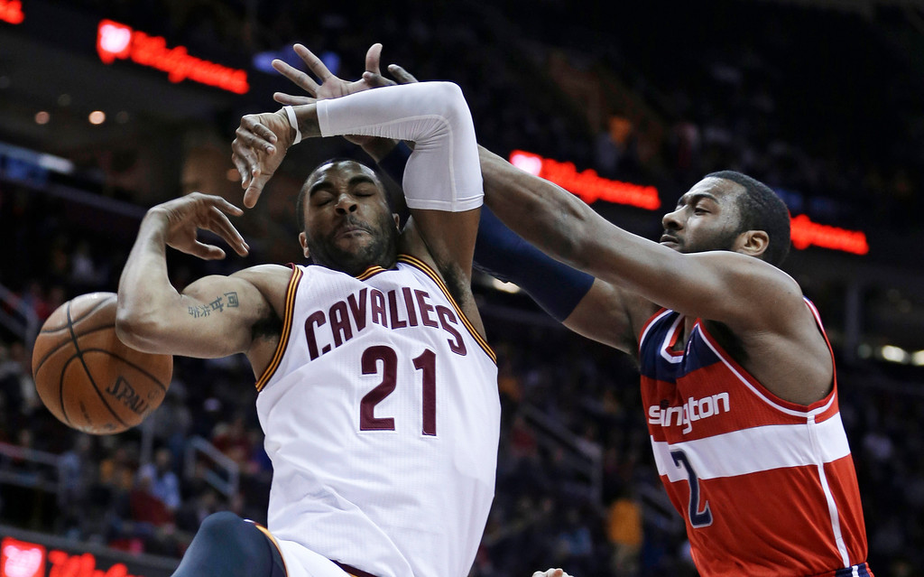 . Cleveland Cavaliers\' Wayne Ellington (21) loses control of the ball under pressure from Washington Wizards\' John Wall (2) during the first quarter of an NBA basketball game Tuesday, March 12, 2013, in Cleveland. (AP Photo/Tony Dejak)