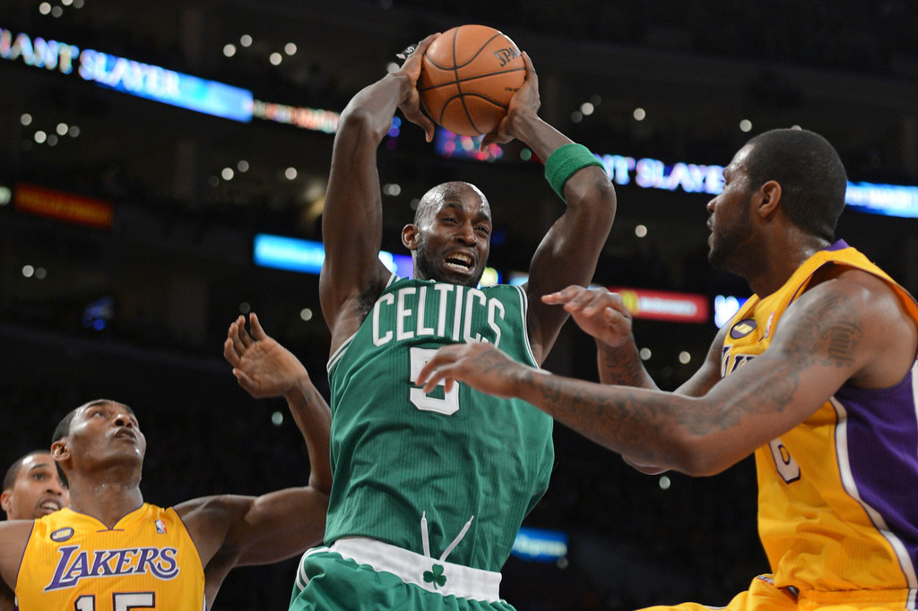 . Celtics\' Kevin Garnett comes up with the rebound as Lakers Metta World Peace and Earl Clark defend during first half action at Staples Wednesday.  Photo by David Crane/Staff Photographer