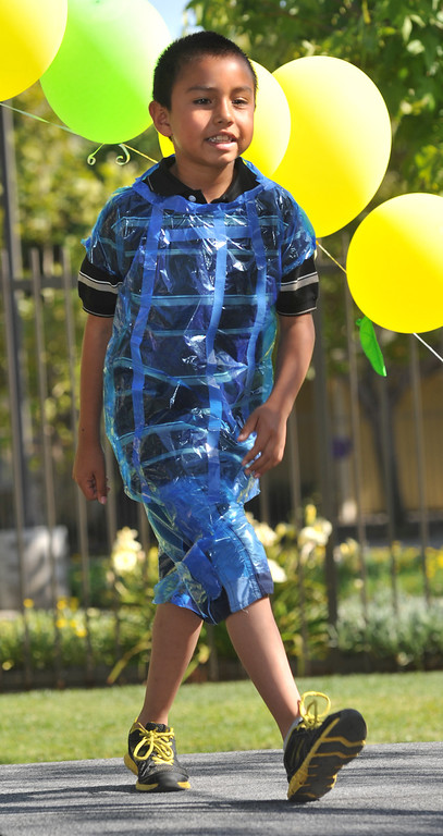 Description of . Angel Vargas, 7, shows his wearable art in the