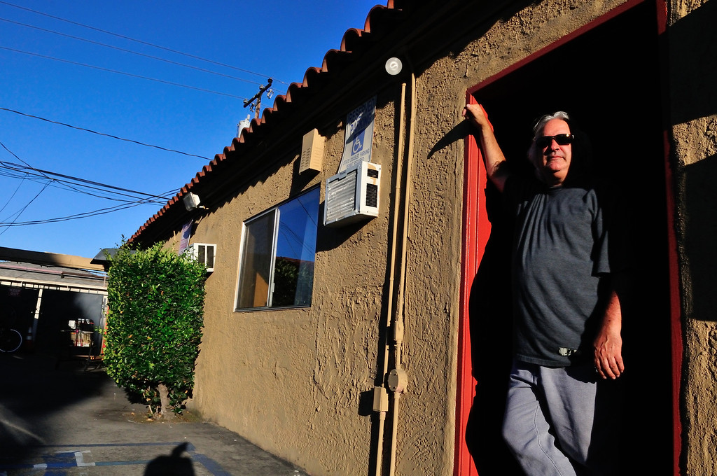 . Tim Grobaty waits for the action from the doorway of his room at the El Capitan Motor Inn.Photo by Thomas Wasper for the Press Telegram
