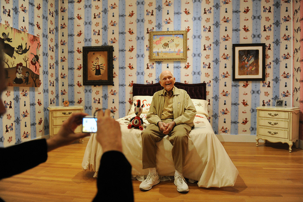 """. Jay Segal is photographed by Gary Baseman on the bed in the bedroom in the exhibition \""""Gary Baseman: The Door is Always Open,\"""" at the Skirball Cultural Center, Wednesday, April 24, 2013. Baseman\'s work is known for his vibrant, cartoon-like, artistic style in publications such as The New Yorker, Rolling Stone and the LA Times. He designed for the game Cranium and created the animated TV series, Teacher�s Pet.The exhibition design is based on his childhood home in LA�s Fairfax district and includes family furniture and snapshots and many items of interior décor designed by the artist, including wallpaper, pillows, a chandelier and more. (Michael Owen Baker/Staff Photographer)"""