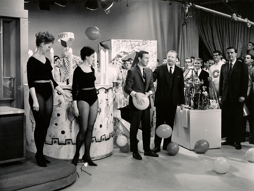 """. In this October 1963 photo courtesy of the Personal Archives of the Skitch Henderson Museum, Skitch Henderson, fourth from left, stands next to \""""Tonight Show\"""" host Johnny Carson, third from left, on the one year anniversary of Carson\'s hosting of the show in New York. Henderson was the bandleader for the show at the time. Carson\'s sidekick Ed McMahon looks on at far right.  (AP Photo/Personal Archives of the Skitch Henderson Museum)"""