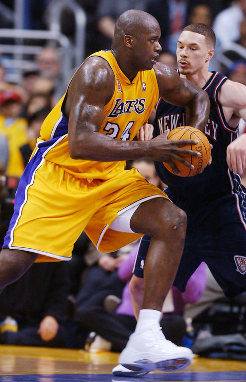 . Los Angeles Lakers\' Shaquille O\'Neal, left, drives by New Jersey Nets\' Aaron Williams during the first half at the Staples Center in Los Angeles, Tuesday, March 5, 2002. O\'Neal scored 40 points in the Lakers\' 101-92 win. (AP Photo/Chris Pizzello)