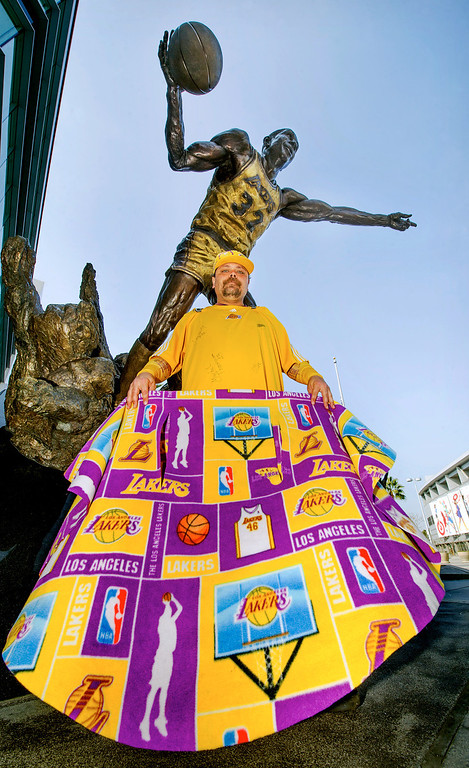 . Paul Casas, of Los angeles, stands before the bronze sculpture of Earvin Magic Johnson, to support  the Jerry Buss\' family and the Lakers over his death, outside the Staples Center in Los Angeles on Monday, Feb. 18, 2013.  Casas, wears a Laker shirt autographed by numerous Laker players of the past, has been a Laker fan for most of his life, attending most home games at the Staples Center. Lakers owner Dr. Jerry Buss died today after a long battle with cancer. He was 80. (SGVN/Photo by Walt Mancini/SXCity)