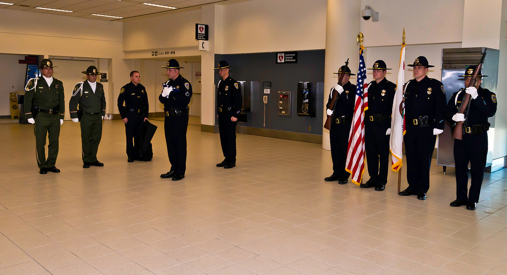 Description of . The U.S. Honor Flag arrives at LA/Ontario International Airport for use at a funeral for a fallen law enforcement officer, Riverside Police Officer Michael Crain in Riverside, California Courtesy Photo