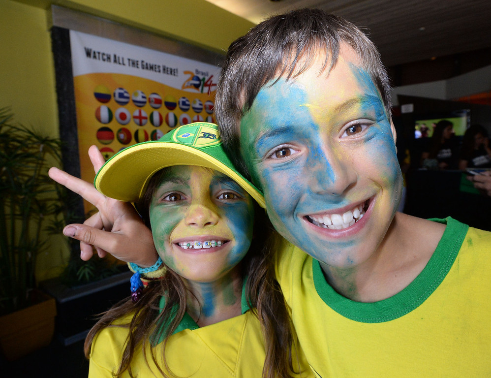 . Young Brazil soccer fans Shayia Ermeti, 8, left and her brother Neymar, 10, came decked-out in Brazilian colors. Shayia even had her braces done in Brazilian colors. Fans crowded into Samba restaurant to watch the FIFA World Cup game against Croatia Thursday, June 12, 2014, Redondo Beach, CA.  The South Bay is home to a large Brazilian community. Photo by Steve McCrank/Daily Breeze