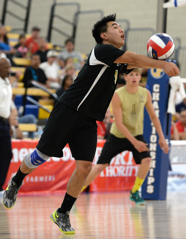 . Bishop Montgomery\'s Andre Labayen (11) bump-sets the ball against Parker in a Southern California Regional Division III Final volleyball match Saturday at Santiago Canyon College in Orange. The match came down to the final points of the fifth game, with Bishop Montgomery losing the heart-breaker. Bishop Montgomery vs. Francis Parker (San Diego) 20130525 Photo by Steve McCrank / Staff Photographer