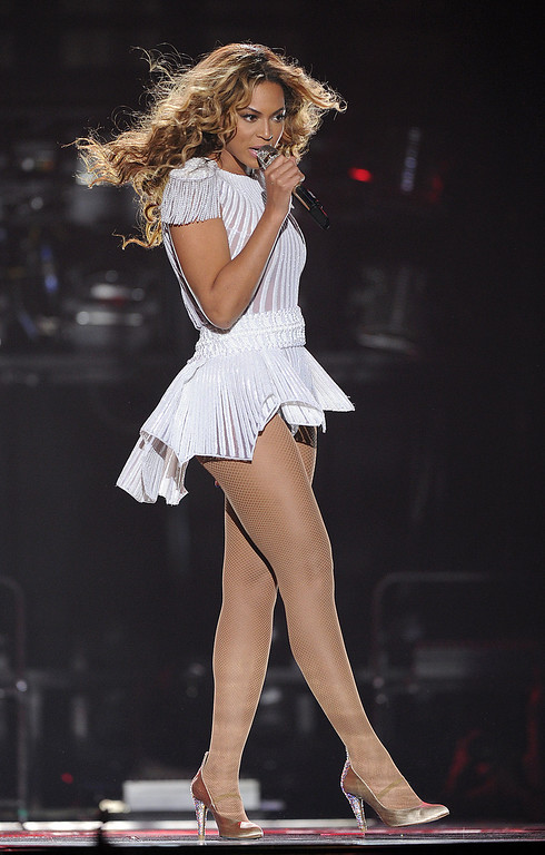 """. IMAGE DISTRIBUTED FOR PARKWOOD ENTERTAINMENT - Singer Beyonce performs on the opening night of her \""""Mrs. Carter Show World Tour 2013\"""", on Monday, April 15, 2013 at the Kombank Arena in Belgrade, Serbia. Beyonce is wearing a custom, hand beaded white peplum one-piece by designers Ralph & Russo. (Photo by Frank Micelotta/Invision for Parkwood Entertainment/AP Images)"""