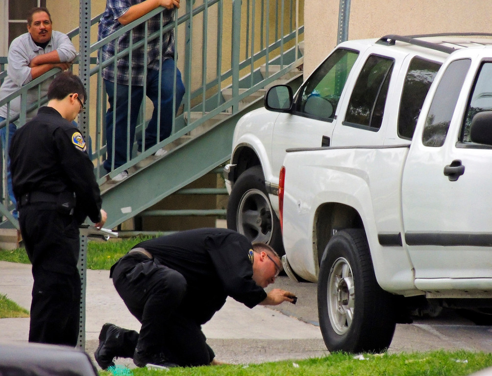 . Police investigate the scene of a double homicide on the 300 block of Orchid Lane in Pomonaon Saturday, April 13, 2013. Two teenagers, a 16-year-old and 13-year-old boy, were fatally shot and one adult male was critically wounded, according to authorities. (Rachel Luna / Staff Photographer)