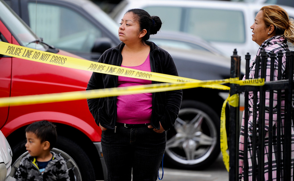. Neighborhood residents watch police investigate the scene of a double homicide on the 300 block of Orchid Lane in Pomonaon Saturday, April 13, 2013. Two teenagers, a 16-year-old and 13-year-old boy, were fatally shot and one adult male was critically wounded, according to authorities. (Rachel Luna / Staff Photographer)
