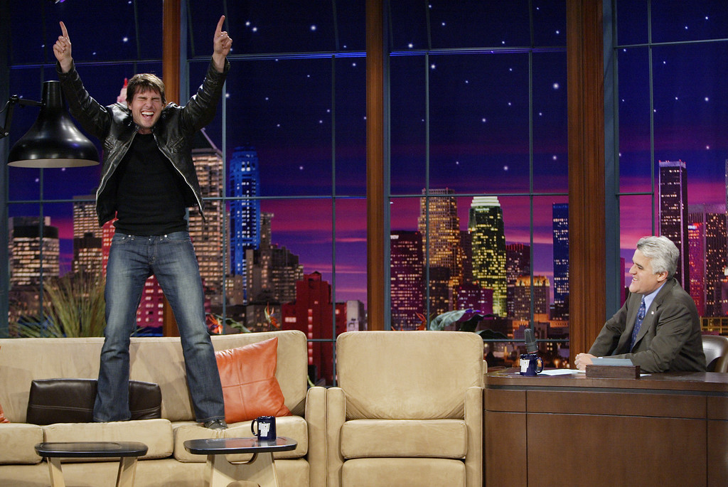 ". In this photo released by NBC, Tom Cruise jumps onto the sofa after greeting host Jay Leno on the set of ""The Tonight Show with Jay Leno,\"" during the taping of the show at NBC studios in Burbank, Calif., on Wednesday, June 8, 2005. When asked about his relationship with Katie Holmes, Cruise said he \""is looking forward to traveling, scuba diving and spending the rest of his life with her.\"" (AP Photo/Paul Drinkwater, NBC)"