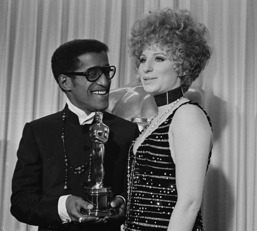 ". Barbra Streisand with Sammy Davis, Jr., who accepted the Oscar for Leslie Bricusse for ""Doctor Dolittle,\"" April 10, 1968 (AP Photo)"