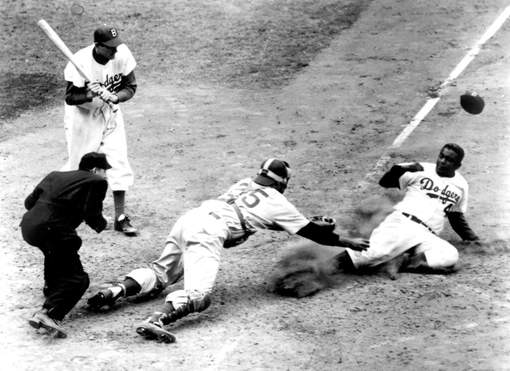 Description of . Jackie Robinson, shown stealing home against the Chicago Cubs in 1952.  Daily News file photo