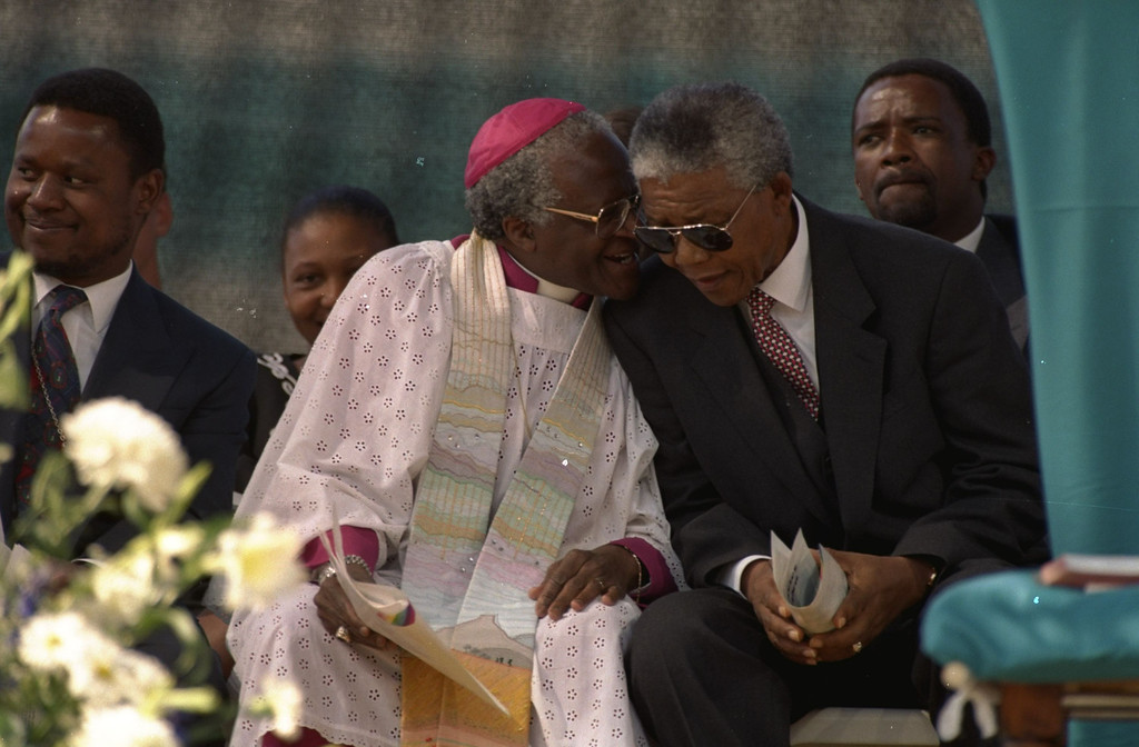 . Archbishop Desmond Tutu, left, and President-elect Nelson Mandela confer during celebrations at a rally held in Soweto, South Africa, Sunday, May 8, 1994 in honor of national Thanksgiving Day.  The event, attended by thousands of supporters of all races, came on the eve of Mandela\'s inauguration as the country\'s first black president.  Others unidentified.  (AP Photo/David Brauchli)
