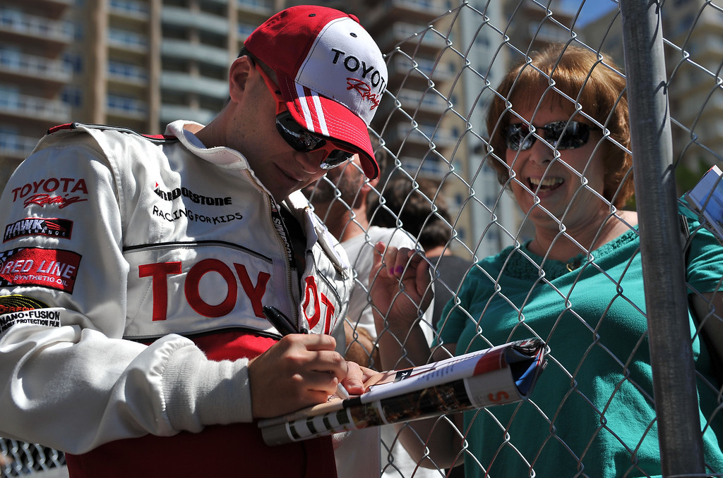 . 4/19/13 - Brett Davern signs an autograph for a fan before the Friday morning practice of the Toyota Pro/Celebrity race at the 39th Annual Toyota Grand Prix of Long Beach. Photo by Brittany Murray / Staff Photographer