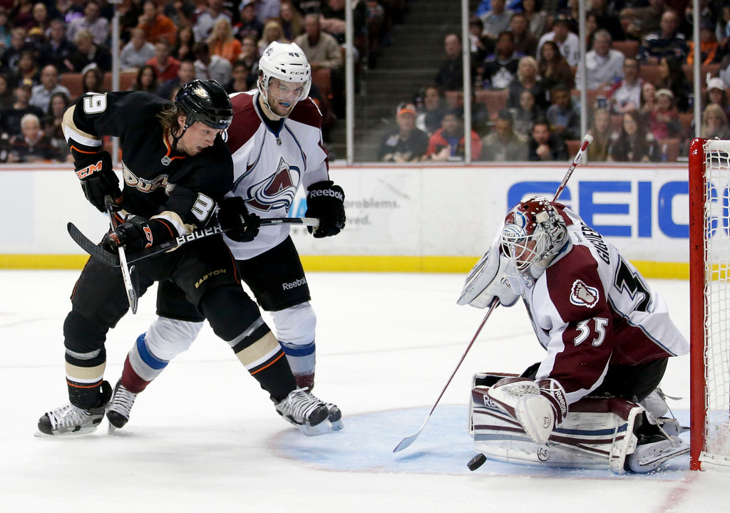 . Colorado Avalanche goalie Jean-Sebastien Giguere, right, makes a save as Anaheim Ducks\' Matt Beleskey, left, and Colorado Avalanche\'s Mark Olver watch during the second period of an NHL hockey game in Anaheim, Calif., Wednesday, April 10, 2013. (AP Photo/Jae C. Hong)