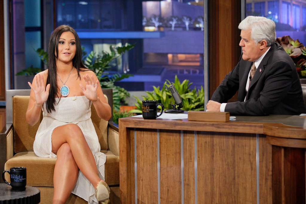 """. This Oct. 30, 2012 photo released by NBC shows Jenni \""""JWoww\"""" Farley, a cast member in the reality series \""""Jersey Shore,\"""" left, and host Jay Leno on \""""The Tonight Show with Jay Leno,\"""" in Burbank, Calif. Seaside Heights, the New Jersey town that for millions made ?Jersey Shore? synonymous with Snooki was among the hardest hit by Superstorm Sandy and its famous summer residents sent their prayers to those affected. Farley and fellow cast members Paul \""""Pauly D\"""" DelVecchio, Vinny Guadagnino asked their Twitter followers to donate to the American Red Cross. (Photo by: Paul Drinkwater/NBC)"""