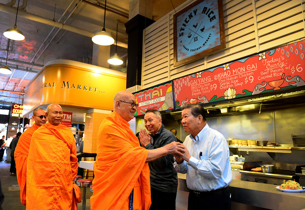 Description of . Wat Thai Temple monks, of North Hollywood, approach Ben Utasee, left, and Suthin Tewasart as they arrive to bless the opening of Sticky Rice at Grand Central Market in downtown Los Angeles Monday, April 30, 2013. Sticky Rice, owned by David Tewasart, of Pasadena, is kicking off the openings of new restaurants at the market. (SGVN/Staff Photo by Sarah Reingewirtz)